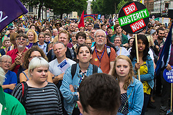 London, June 20th 2015. Thousands of people converge on the streets of London to join the People's Assembly Against Austerity's march from the Bank of England to Parliament Square. PICTURED: The crowd listens to speakers' messages relayed from the stage to a big screen on Whitehall.