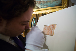 London, July 3rd 2017. A Bonhams gallery assistant examines the newly rediscovered Parmigianino 'AA sketch of three female nudes', estimated at £15-20,000 in their forthcoming Old Master Paintings sale.