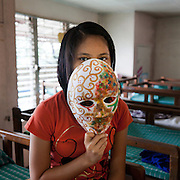 "Shanon, 16. (Not her real name).She is happy to be in the home for the protection it gives and for the hope it has brought back to her. She loves reading and to dance, listening to music and play the guitar. She has choreographed many of the dance performances the girls do in the home to great applause by the audience. She wants to be  Video Jockey(VJ) to help the other children in the home. She wants to work in TV as a place to highlight the issues and lives the children go through...""The curly gold on the left side of the mask signifies all the positive things which have happened in my life. The mixed colours  all the confusion and problems which are happening in my life which at the moment are overpowering my life. I hope some day it will be different, that it will be the other way around. ..Laura Vicuña Foundation, Inc. provides a safe haven, a secure home for girls where they live together with sisters from the Don Bosco order. They get the love and care they never have received and counselling when needed from qualified psychotherapists. .The Laura Vicuña Centre in Cubao houses 30 street girls who may be orphaned, neglected, abandoned, battered, morally endangered and sexually abused.The girls are aged between 6 and 16 and all of them go to school in the local municipality."