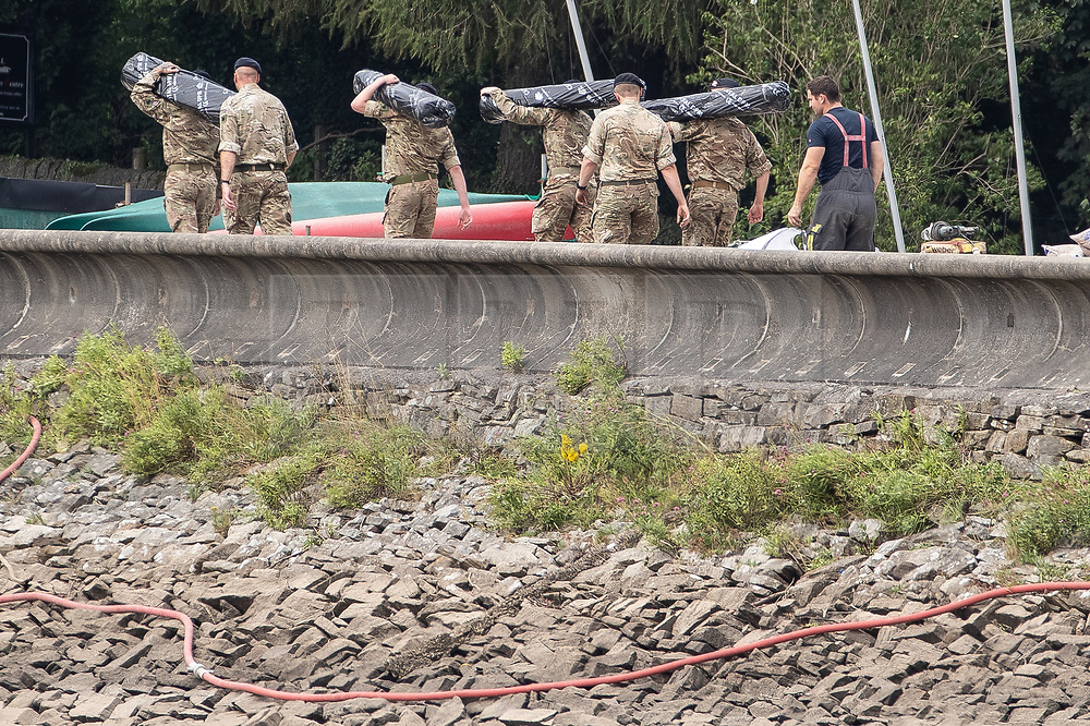 © Licensed to London News Pictures. 04/08/2019. Whaley Bridge, UK. Soldiers carrying rolls of damp proof membrane are seen crossing the reservoir . Watermarks on the rocks show the amount of water that has been pumped away since yesterday (Saturday 3rd August) . More rain is forecast today (Sunday 4th August) in the town of Whaley Bridge in Derbyshire after earlier heavy rain caused damage to the Toddbrook Reservoir , threatening homes and businesses with flooding. Photo credit: Joel Goodman/LNP
