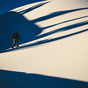 Tyler Hatcher skins in the Cascade Mountains in early morning light with shadows across the snow.