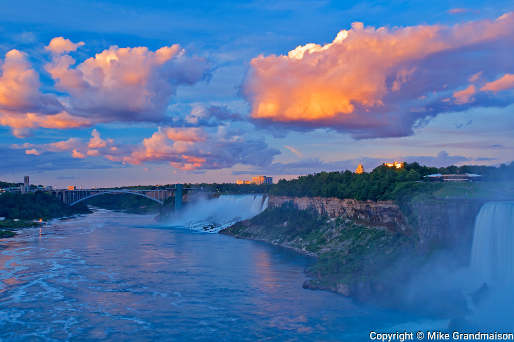 Storm clouds at sunrise with fog as The Niagara River plunges over Niagara Falls.  Golden Horseshoe. Niagara Peninsula.<br />