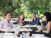 Two couples drinking at outdoor cafe focus on far couple