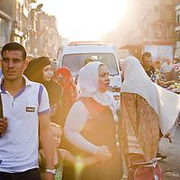 Women make their way through an impoverished neighborhood in Cairo, Egypt. September 2012.