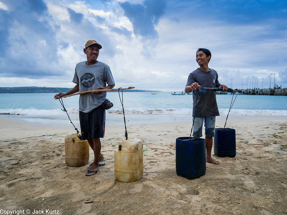 18 JULY 2016 - KUTA, BALI, INDONESIA:  Workers in the fish market at Pasar Ikan pantai Kedonganan gets sea water from the ocean to pour over fish for sale in the market.   PHOTO BY JACK KURTZ