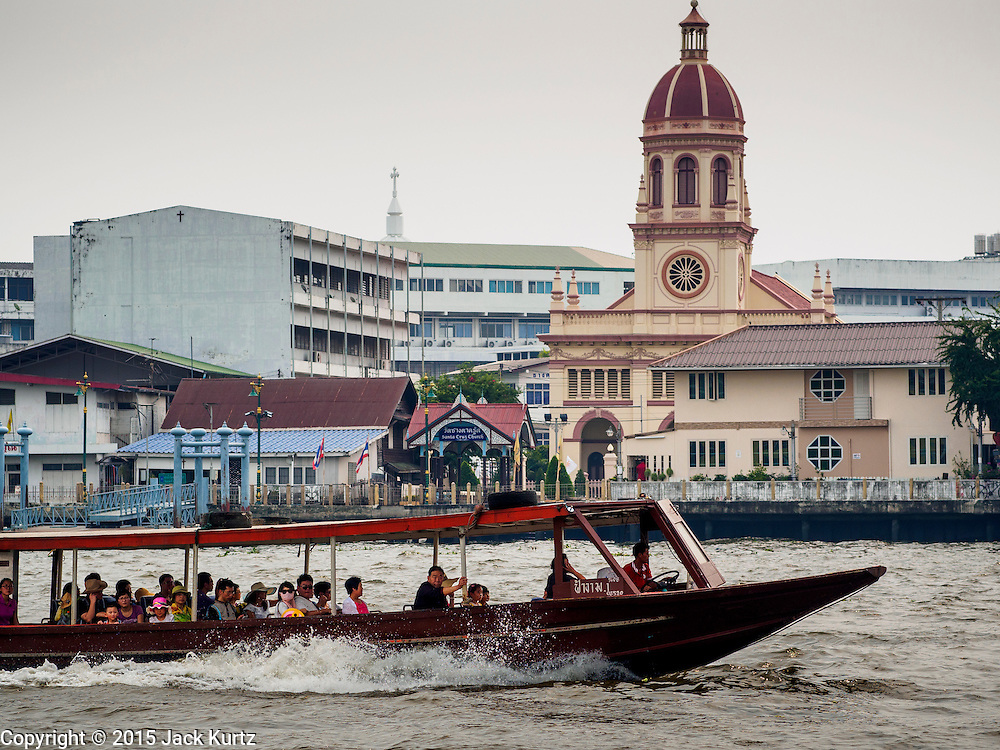 11 FEBRUARY 2015 - BANGKOK, THAILAND: A tourist boat on the Chao Phraya River passes Santa Cruz Catholic Church in the Thonburi section of Bangkok. There has been a Catholic church on the site since 1770. The current church was finished in 1916. It is one of the oldest Catholic churches in Thailand. Now the neighborhood around the church is known for the Thai adaptation of Portuguese cakes baked in the neighborhood. Several hundred Siamese (Thai) Buddhists converted to Catholicism in the 1770s. Some of the families started baking the cakes. When the Siamese Empire in Ayutthaya was sacked by the Burmese, the Portuguese and Thai Catholics fled to Thonburi, in what is now Bangkok. The Portuguese established a Catholic church near the new Siamese capital. There are still a large number of Thai Catholics living in the neighborhood around the church.     PHOTO BY JACK KURTZ