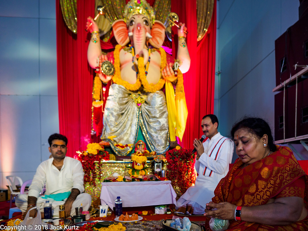 """23 SEPTEMBER 2018 - BANGKOK, THAILAND:  Prayers and blessings at the Ganesha Festival at Wat Dan in Bangkok. Ganesha Chaturthi also known as Vinayaka Chaturthi, is the Hindu festival celebrated on the day of the re-birth of Lord Ganesha, the son of Shiva and Parvati. The festival, also known as Ganeshotsav (""""festival of Ganesha"""") is observed in the Hindu calendar month of Bhaadrapada, starting on the the fourth day of the waxing moon. The festival lasts for 10 days, ending on the fourteenth day of the waxing moon. Outside India, it is celebrated widely in Nepal and by Hindus in the United States, Canada, Mauritius, Singapore, Thailand, Cambodia, and Burma.  PHOTO BY JACK KURTZ"""