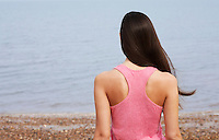Young woman standing on beach back view