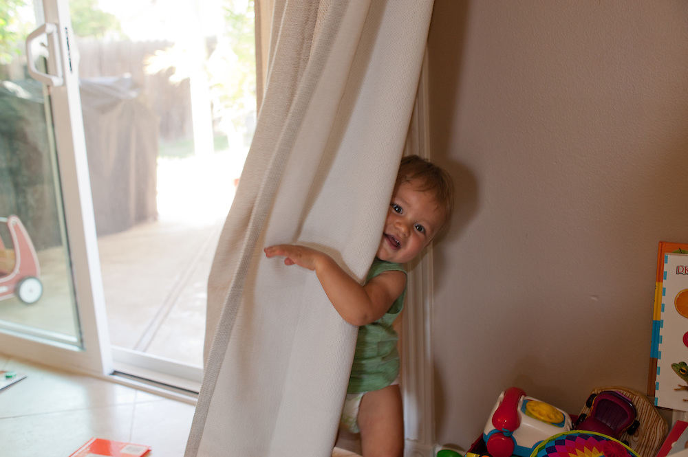 Little boy playing hide-and-seek behind a curtain in the living room