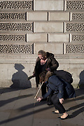 A woman stoops to retrieve the hand strap of her friend's walking stick in Parliament Square SW1, Westminster, on 29th January 2020, in London, England.