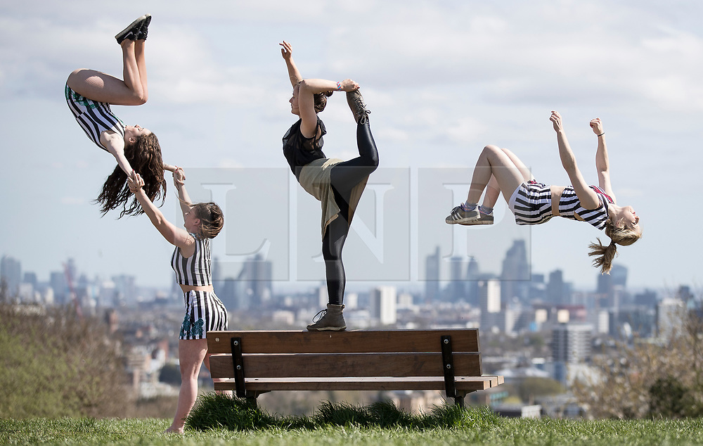 © Licensed to London News Pictures. 17/04/2018. London, UK. Members of 'No Show' and 'The Bekkrell Effect' all female acrobatic troupes perform in sight of the London skyline from Parliament Hill in warm afternoon sunshine. 'No Show'  and The Bekkrell Effect are performing in the third week of CircusFest at The Roundhouse in Camden. Photo credit: Peter Macdiarmid/LNP