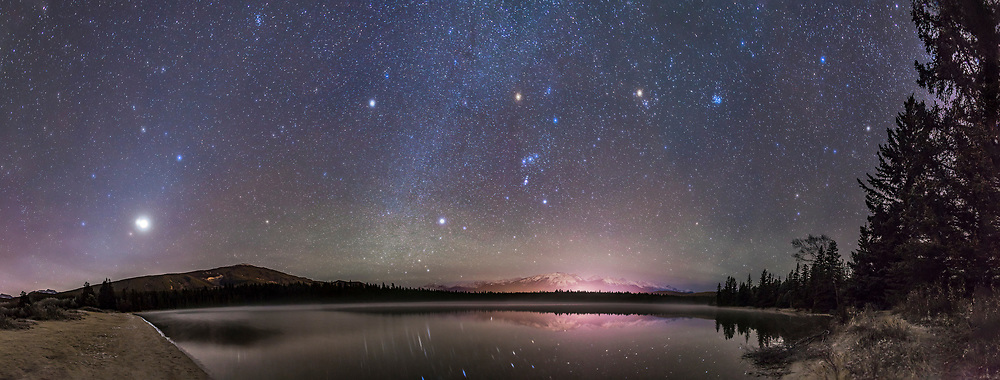 A panorama of roughly 180&deg; showing a star- and planet-filled sky in the pre-dawn hours over Lake Annette in Jasper National Park, Alberta, on the morning of October 25, 2015. <br /> <br /> At left, to the east, are the two bright planets, Venus (brightest) and Jupiter in a close conjunction 1&deg; apart (and here almost merging into one glow), plus reddish Mars below them, all in Leo, with the bright star Regulus above them. At centre, to the south, is Orion and Canis Major, with the bright star Sirius low in the south. At upper right are the stars of Taurus, including Aldebaran and the Pleiades star cluster. Venus was near greatest elongation on this morning. <br /> <br /> The Milky Way runs vertically at centre, between Sirius and Procyon, the bright star above centre. The faint glow of morning Zodiacal Light rises in a diagonal band at left in the east through the planets and stars of Leo and into Cancer and the Beehive Cluster at top left. <br /> <br /> No special filter was employed here &mdash; the hazy planets and stars and colourful star images comes naturally from a high haze over the sky this morning. It bloats the images of Venus and Jupiter so they almost merge. <br /> <br /> The stars are partly reflected in the waters with wind distorting some of the reflections. Some green airglow appears in the south as well.<br /> <br /> Distant Whistler peak below Orion is lit by lights from the Jasper Townsite. The site is the shore of Lake Annette near the Jasper Park Lodge and site to the annual star party held as part of the Jasper Dark Sky Festival. I shot this scene the morning after the 2015 Festival.<br /> <br /> This is a panorama of 12 segments, shot with the 24mm lens mounted vertically (portrait), each for 30 seconds at f/2.8 with the Canon 6D at ISO 3200. Stitched with Photoshop, with some vertical scaling to reduce the distortion introduced by the pan mapping process.