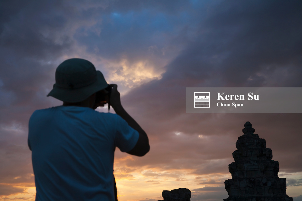 Tourist photographing the ruins on Bakheng Hill at sunset, UNESCO World Heritage site.