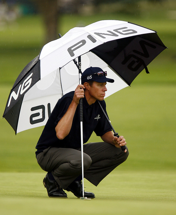 Nick O'Hern of Australia waits under an umbrella on the green on the twelveth hole during the first day of the US Open Golf Championship at Winged Foot Golf Club in Mamaroneck, New York Thursday, 15 June 2006.