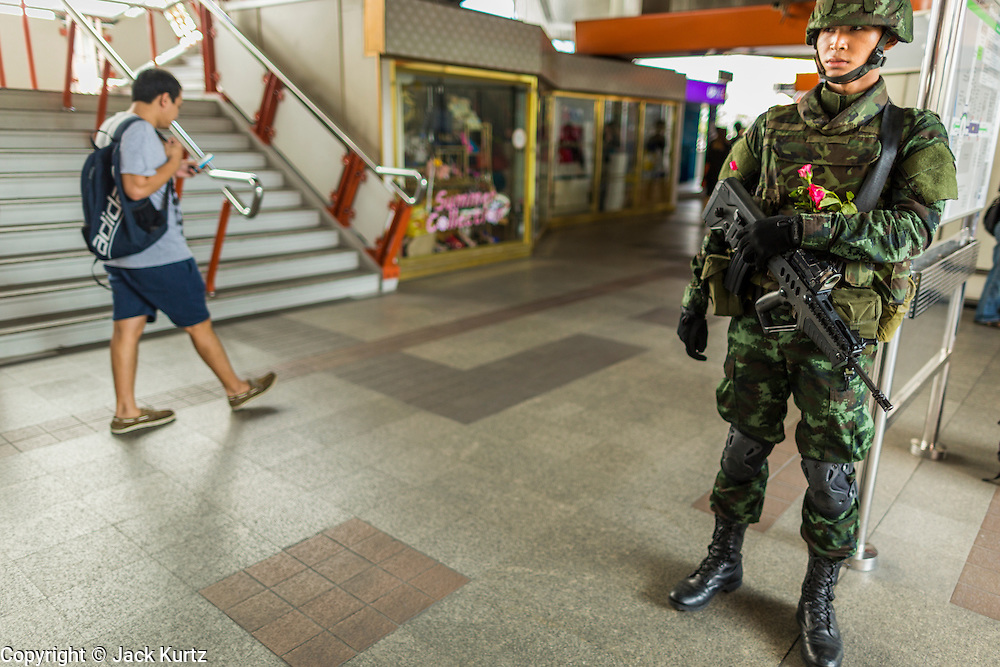 26 MAY 2014 - BANGKOK, THAILAND:    A Thai soldier on duty in the Victory Monument BTS Skytrain station. The station, along with other stations in the area, was shut down Monday afternoon in anticipation of pro-democracy protestors. About two thousand people protested against the coup in Bangkok. It was the third straight day of large pro-democracy rallies in the Thai capital as the army continued to tighten its grip on Thai life.    PHOTO BY JACK KURTZ