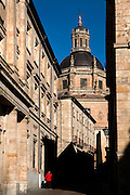 """Low angle view of the dome of the Clerecia Church,  Salamanca, Spain, seen through the surrounding buildings on December 18, 2010 at midday. The Baroque style Clerecia Church, originally the Royal College of the Company of Jesus, was commissioned in the 17th century, from architect Juan Gomez de Mora, by Queen Margarita of Austria, wife of Philip III of Spain. It comprises two sections: the Jesuit school and church, with its three-storey Baroque cloister, and private living quarters for the monks and now houses the Salamanca Pontificia University. Salamanca, an important Spanish University city, is known as La Ciudad Dorada (""""The golden city"""") because of the unique golden colour of its Renaissance sandstone buildings. Founded in 1218 its University is still one of the most important in Spain. Around it the Old Town is a UNESCO World Heritage Site. Picture by Manuel Cohen"""