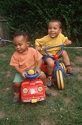 Two young brothers playing on bike and truck outside in park,