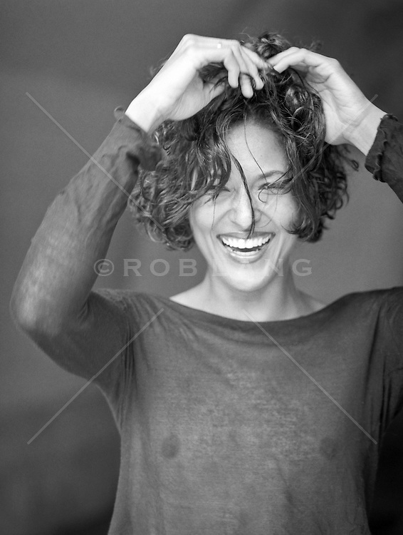 beautiful woman laughing while touching her hair