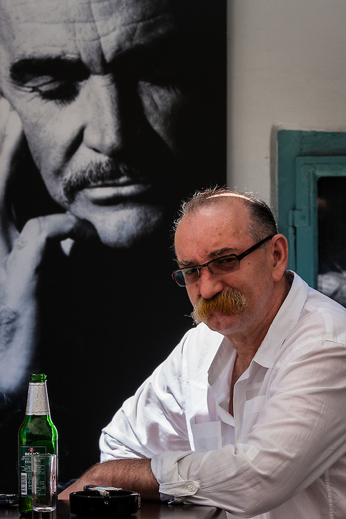In Zagreb, a man sits on a bar near a poster of Sean Connery