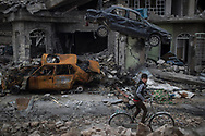 A boy rides his bike past destroyed cars and houses in a neighbourhood recently liberated by Iraqi security forces on the western side of Mosul, Iraq, Sunday, March 19, 2017. (AP Photo/Felipe Dana)