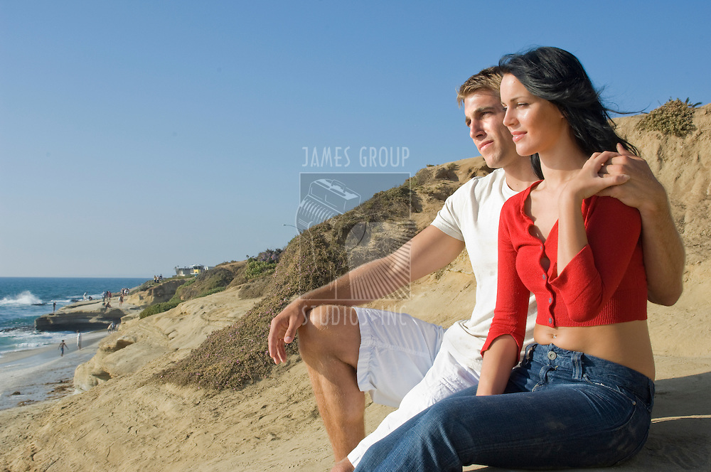 Attractive, young couple sitting on the bluffs overlooking the Pacific Ocean