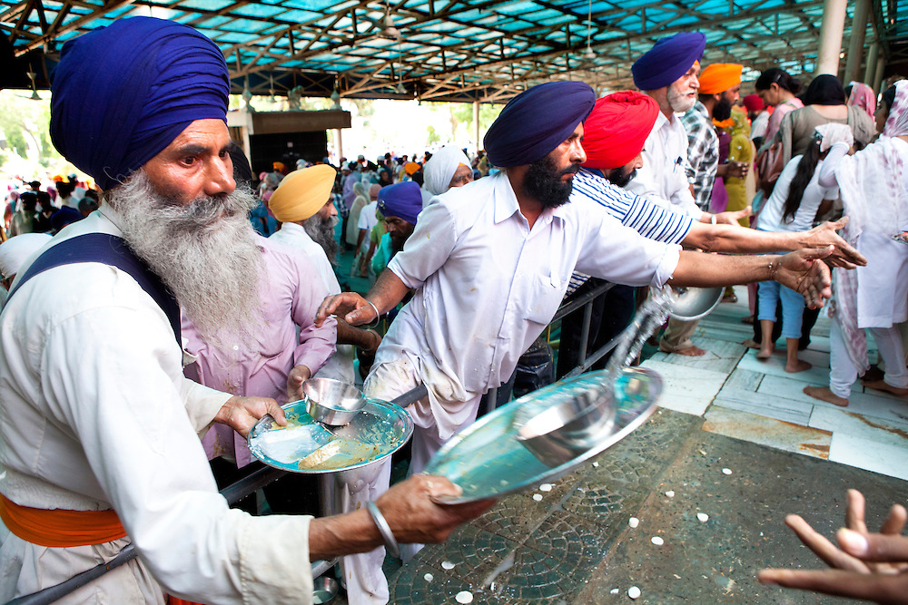 Sikh believers volunteer to clean the dishes at the golden temple. At the golden temple tens of thousand free meals are served per day. The main kitchen workers are pilgrims that volunteer.