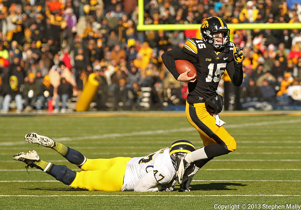 November 23 2013: Iowa Hawkeyes quarterback Jake Rudock (15) is tripped up by Michigan Wolverines linebacker Jake Ryan (47) as he scrambles with the ball during the first quarter of the NCAA football game between the Michigan Wolverines and the Iowa Hawkeyes at Kinnick Stadium in Iowa City, Iowa on November 23, 2013. Iowa defeated Michigan 24-21.