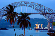 At dawn a red cargo ship passes quietly under the Bridge Of The Americas, the Pacific entrance to Panama Canal in Panama.