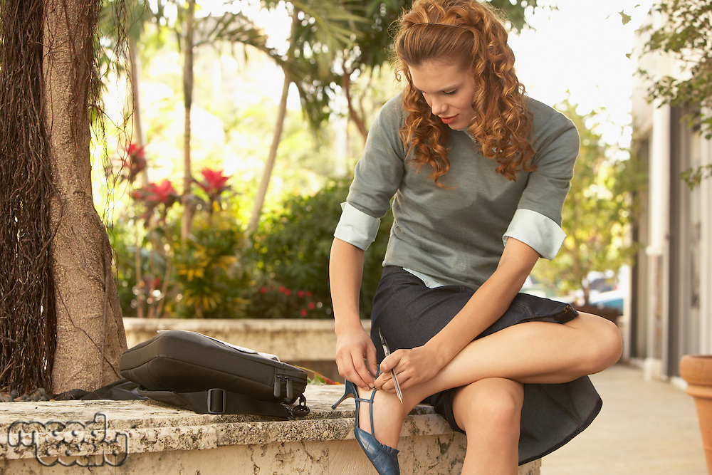 Young woman adjusting shoe in street