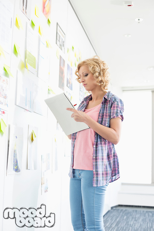 Creative businesswoman writing notes by papers stuck on wall in office