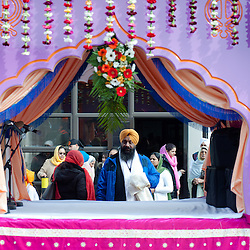 London, UK - 7 April 2013: A Sikh man stands behind the float used for the celebration.