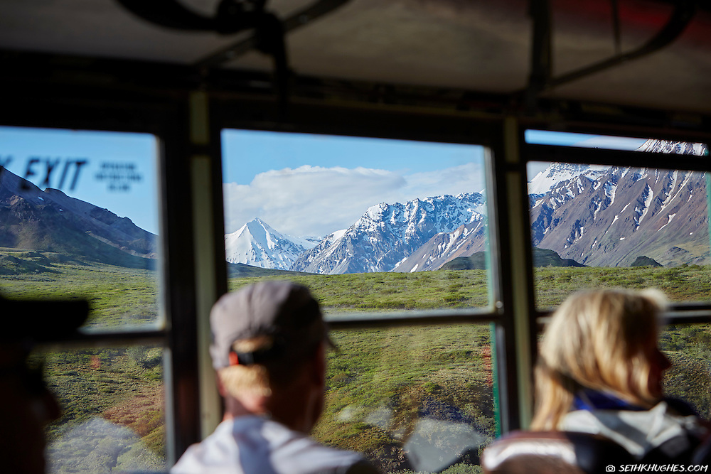 Tourists admire the view through a tour bus window while traveling the Denali Park Road in Alaska.