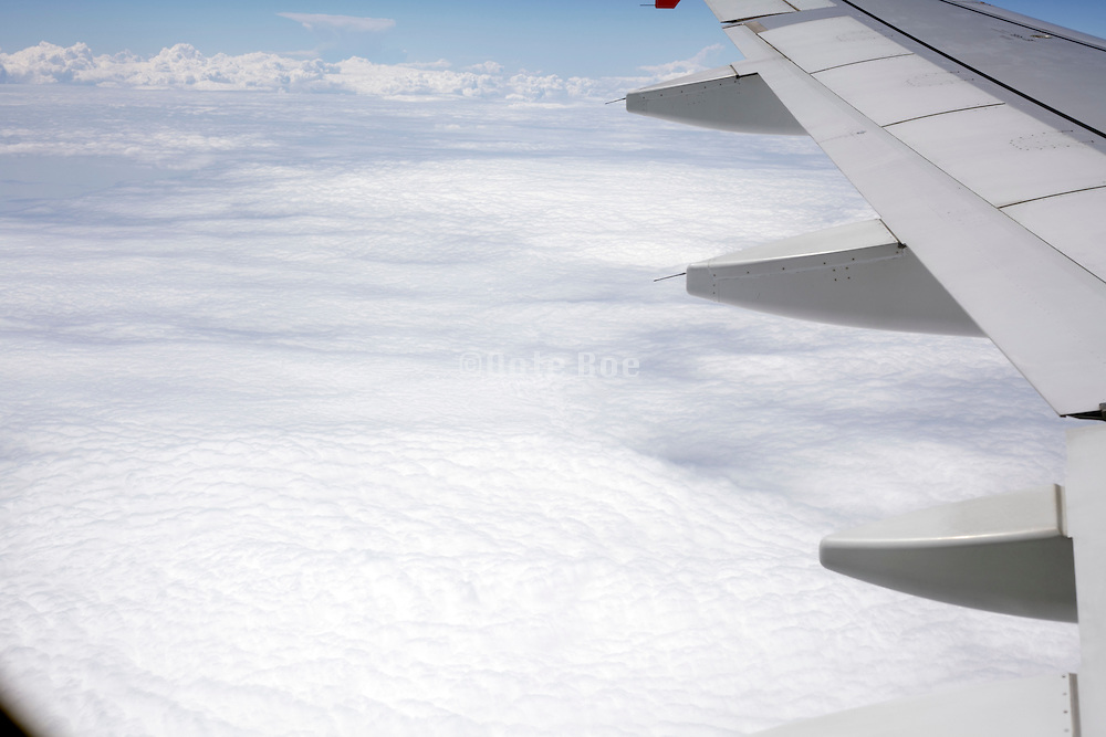 view from airplane flying above the clouds
