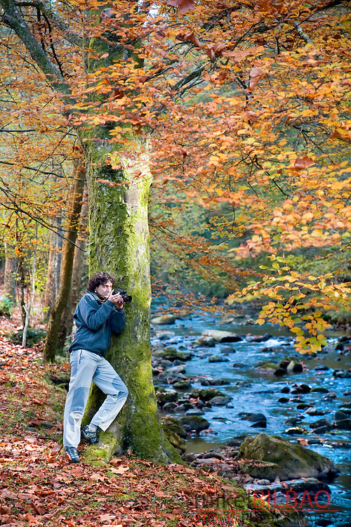 young woman taking photographs of a forest in autumn.<br /> Cabuerniga Valley, Cantabria, Spain, Europe.