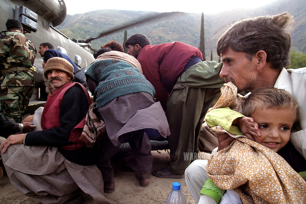 A earthquake survivors wait to board a US Army Chinook for evacuation from earthquake-stricken northern Pakistan, October 18, 2005, Kashmir, Pakistan. The South Asia earthquake measured 7.6 on the Richter Scale in Pakistan Administered Kashmir just before 9am on Saturday, October 8, 2005 and is the twelfth most destructive earthquake in recorded history, killing 87,000 and internally displacing 3 million. Early assessments indicate it will take upwards of 10 years for the affected regions to fully recover from the damage, however, scientists estimate the region should prepare for future earthquakes on a much larger scale, citing the Eurasian and Indian tectonic plates running through Kashmir as extremely unstable. (Photo by Warrick Page)
