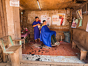 11 MARCH 2016 - LUANG PRABANG, LAOS: A barber gives a man a shave in the community of Chomphet, across the Mekong River from Luang Prabang. Laos is one of the poorest countries in Southeast Asia. Tourism and hydroelectric dams along the rivers that run through the country are driving the legal economy.       PHOTO BY JACK KURTZ