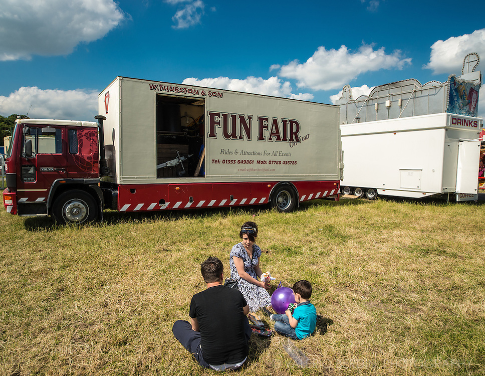 A family has a picnic in an empty spot on a grass next to the many trucks taking itinerant attractions to summer fairs.