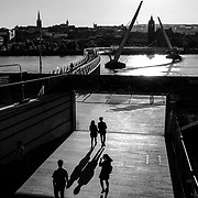 As sunset gives way to a Friday night, pedestrians cross the Peace Bridge over the River Foyle in Londonderry. Northern Ireland, September 2019