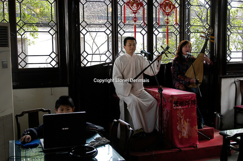 A boy plays with his computer while his father sings ancient songs in traditional Suzhou tea house.