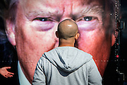 A man looks at a picture of Donald Trump outside the debate area at the Hofstra University. The Democrate and Republican nominees for US President, Hillary Rodham Clinton and Donald John Trump, met on Sep. 26th for the first head to head Presidential Debate at the Hofstra University in Long Island.