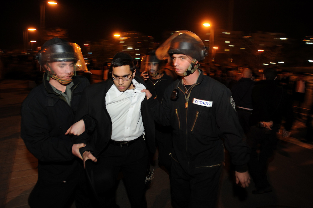 An Ultra-Orthodox Jewish man is being arrested by Israeli policemen during a protest near Intel Corp's electronic chip plant in Jerusalem December 27, 2009. Thousands of Ultra-orthodox Jews demonstrated on against the operation of the plant on the Jewish Sabbath.