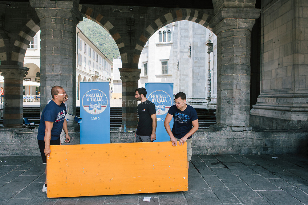 COMO, ITALY - 21 JUNE 2017: Technicians unmount a table at the end of Mario Landriscina's rally,  the leading candidate for mayor of Como after the first round of voting to replace the left-leaning mayor, here at the Broletto, a medieval building next to the Cathedral in Como, Italy, on June 21st 2017. Mr Landriscina wants to close the reception centers.<br /> <br /> Residents of Como are worried that funds redirected to migrants deprived the town&rsquo;s handicapped of services and complained that any protest prompted accusations of racism.<br /> <br /> Throughout Italy, run-off mayoral elections on Sunday will be considered bellwethers for upcoming national elections and immigration has again emerged as a burning issue.<br /> <br /> Italy has registered more than 70,000 migrants this year, 27 percent more than it did by this time in 2016, when a record 181,000 migrants arrived. Waves of migrants continue to make the perilous, and often fatal, crossing to southern Italy from Africa, South Asia and the Middle East, seeing Italy as the gateway to Europe.<br /> <br /> While migrants spoke of their appreciation of Italy&rsquo;s humanitarian efforts to save them from the Mediterranean Sea, they also expressed exhaustion with the country&rsquo;s intricate web of permits and papers and European rules that required them to stay in the country that first documented them.