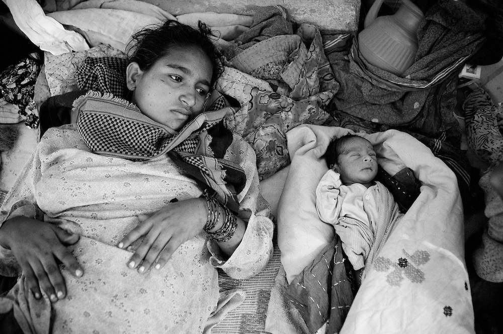 Exhausted and with hardly any time to rest, Hamida lays next to her newborn baby. She returned back to the camp one day after the delivery and immediately had to take up her role as caretaker for her other 3 children besides taking care of the baby. Karachi, Pakistan, 2010