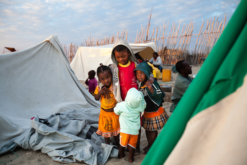 Migrant children lend each other support while their parents set up camp during their annual migration. Families leave their homes with just a few essential belongings that they can fit in their outrigger sailing canoes - fishing gear, rice, drinking water, cooking pots and a few clothes and blankets. They sail for hundreds of kilometres northwards, camping as they go along in tents made using their sails, masts and paddles.