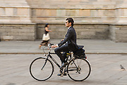 Office worker on bicycle in the streets of Milan, Italy