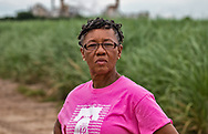 Barbara Washington in front of a sugar cane field next to Mosaic's chemical plant in Convent, Louisiana/