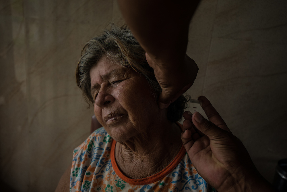 TUMERERO, VENEZUELA - MAY 25, 2016:  Hermelinda Quinbayo, who works in the El Tigre gold mine, gets her ear pricked during a blood test for malaria at a clinic in Tumerero. The spread of malaria in Venezuela is a state secret. Since 2007, the government has not submitted annual epidemiological reports on the disease and says there is no epidemic. But the most recent report, obtained by The New York Times from Venezuelan doctors involved in compiling it, confirms a surge is underway.  Last year, malaria cases rose 56% to 136,000 cases, the highest level in 75 years when the state began efforts to eradicate the disease, according to the report. Malaria has cut a wide swath through the country with cases now present in half of its 23 states. And among the strains present here is Plasmodim falciparum, the most fatal and severe form of the disease. PHOTO: Meridith Kohut for The New York Times