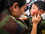 "14 JANUARY 2017 - BANGKOK, THAILAND: Royal Thai Army medical personnel use theatrical make up to put fake ""battlefield injuries"" on children during Children's Day activities at the King's Guard, 2nd Cavalry Division base in Bangkok. Thailand National Children's Day is celebrated on the second Saturday in January. Known as ""Wan Dek"" in Thailand, Children's Day is celebrated to give children the opportunity to have fun and to create awareness about their significant role towards the development of the country. Many government offices open to tours and military bases hold special children's day events. It was established as a holiday in 1955.        PHOTO BY JACK KURTZ"