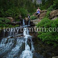 dramatic yoga pose near alpine waterfall