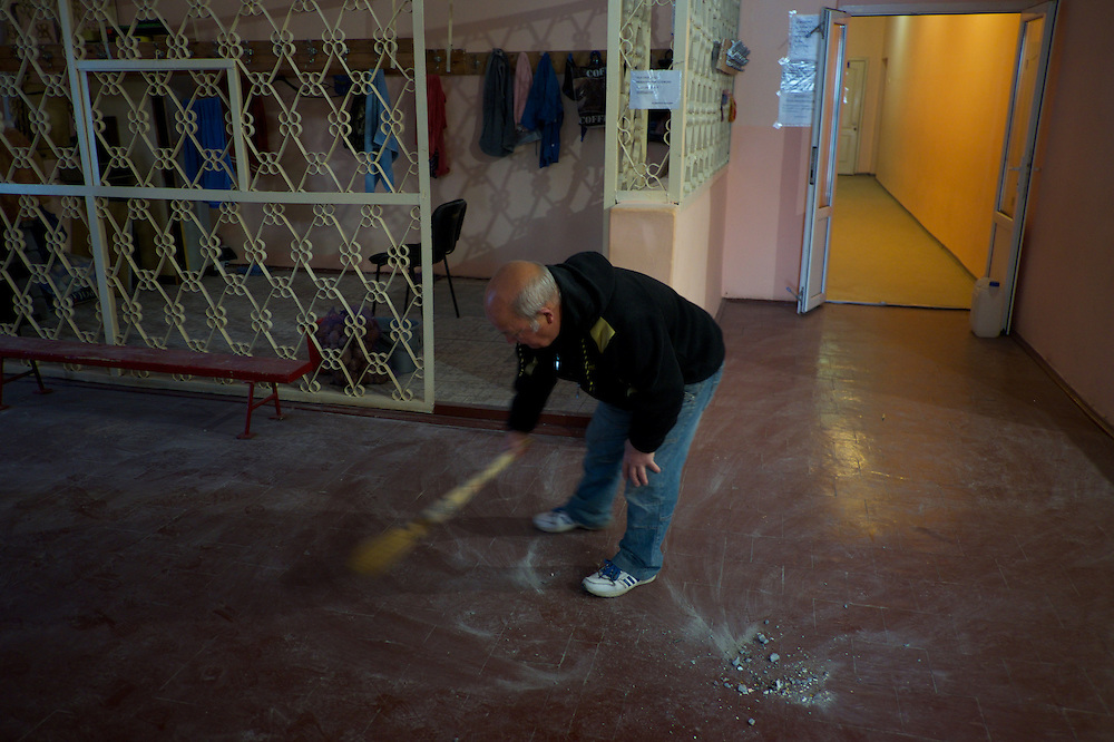 DONETSK, UKRAINE - OCTOBER 19, 2014: A staff member of School 61 in central Donetsk, cleans the rubble from a room of the building hours after it was hit by shellfire presumably shot by the Ukrainian National Guard during fighting for the control of the city's airport area. CREDIT: Paulo Nunes dos Santos